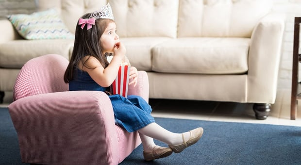 A little girl wearing a tiara and eating popcorn while watching the TV