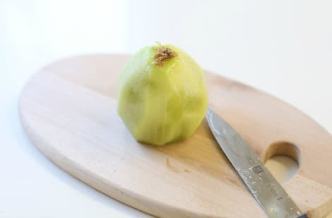 A peeled kiwi on a cutting board