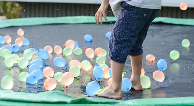A little boy on a trampoline with water balloons on it.
