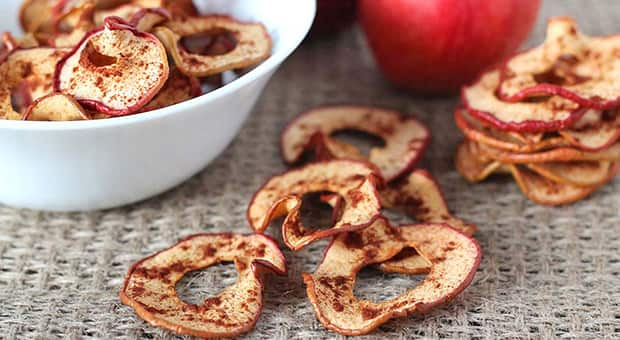 Cinnamon apple slices in a bowl, with a few chips on the table.