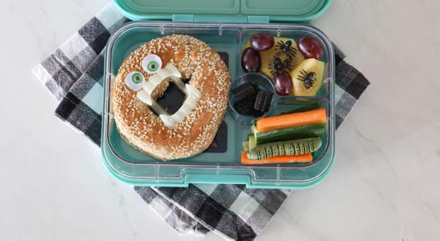A bagel monster with cut up veggies, fruit and creepy crawler toys!