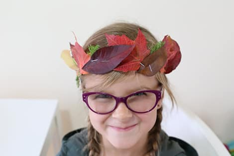 a little girl smiling and wearing the leaf crown she created