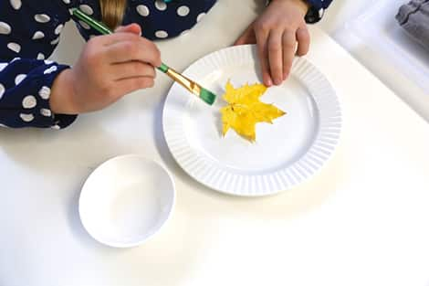 girl painting leaf with a paintbrush