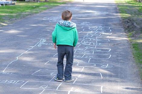 Little boy plays hopscotch.