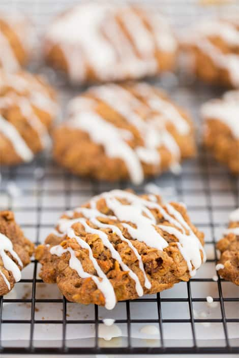Carrot Cake Oatmeal Cookies with icing cooling on a rack.