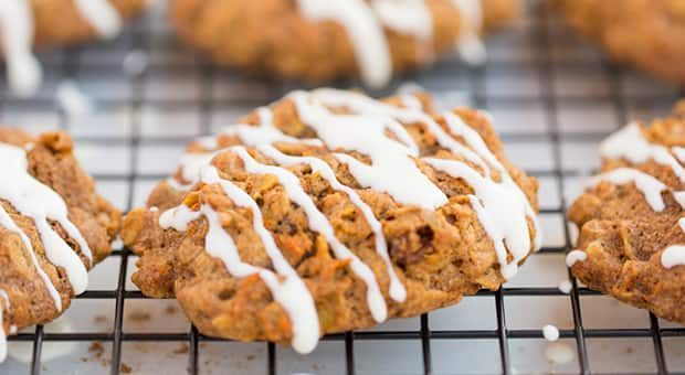 Carrot cake oatmeal cookie drizzled with icing cools on cookie rack.