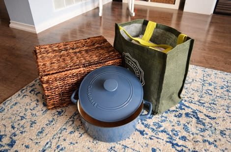 A basket of items, dutch oven and bag of books
