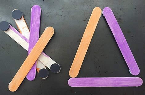 Colourful popsicle sticks with magnets on the ends form a triangle shape.