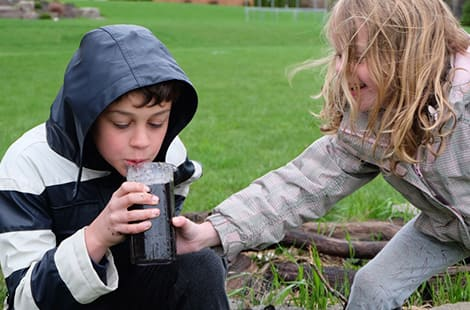 Kids pretend to slurp their mud slushies.