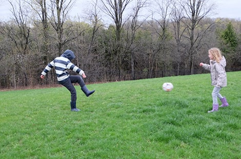 Kids play soccer in the rain.