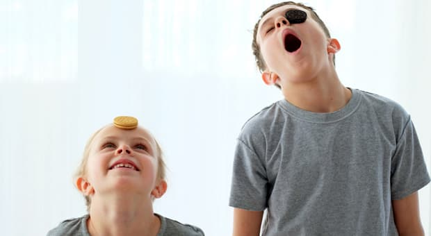 Two children, each with an Oreo cookie on their face, trying to move it down into their mouths without using their hands