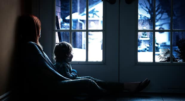 Mother and child sitting by a glass door and looking at the winter scene outside