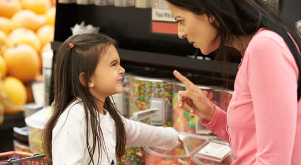 A mother telling her daughter not to grab candy from the dispenser in the store
