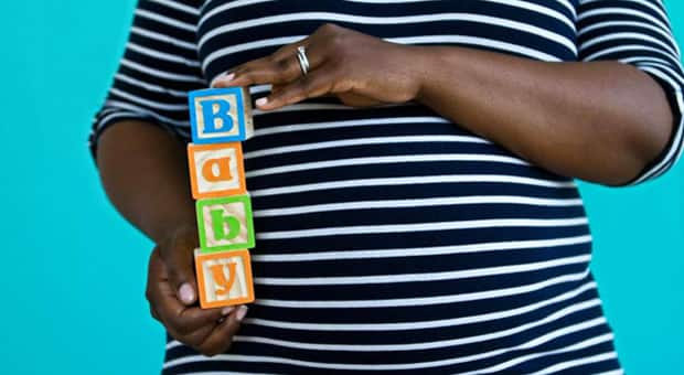 A pregnant woman holding play blocks with letters on them that spell out