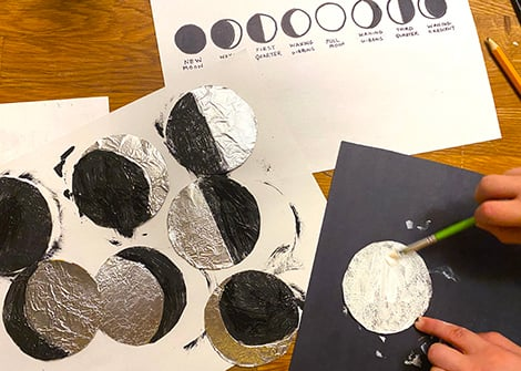 painting the foil-covered circles in black and white based on the moon phases