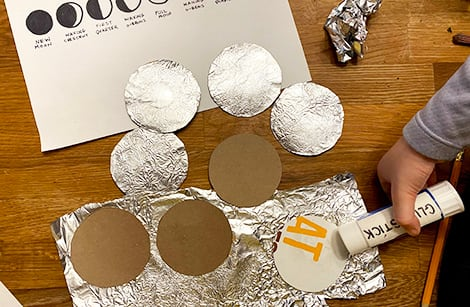 gluing cereal box circles onto the crumpled aluminum foil and cutting them out so you have foil-covered circles