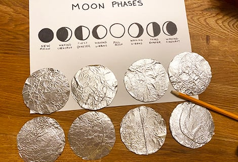 indenting crescent shapes onto the foil-covered circles to match the phases of the moon