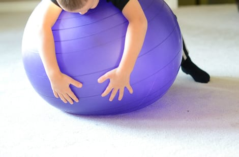 A child balancing on the top of the ball on his tummy