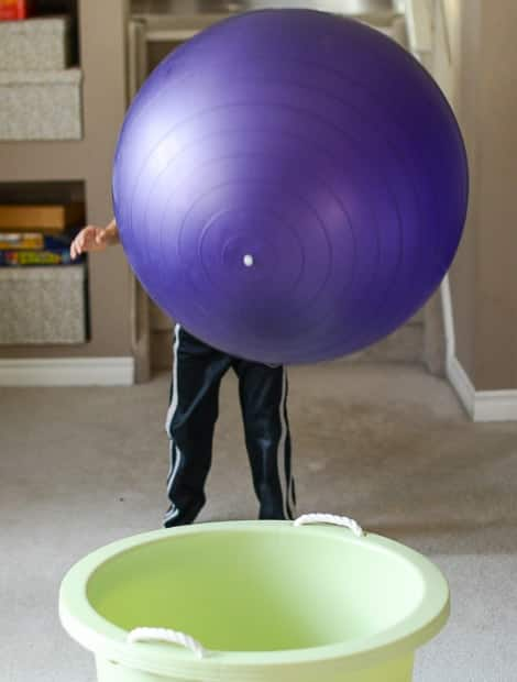 A child throwing the ball into a basket