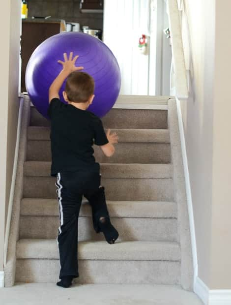 A child rolling the ball up a small flight of stairs
