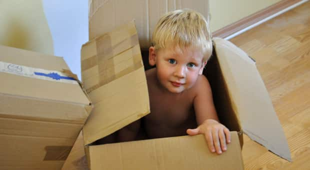 A little boy playing in moving boxes