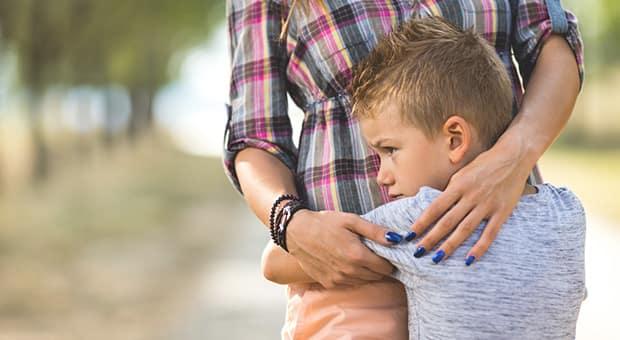 Child hugging mother around the waist.