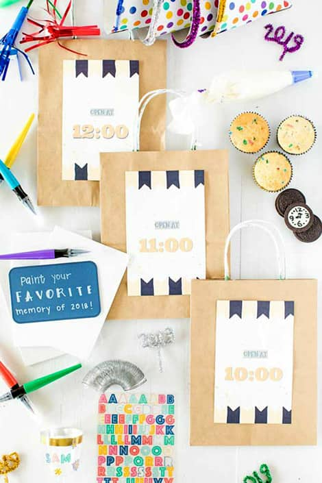 Paper bags with times printed on them with party items and cupcakes around them
