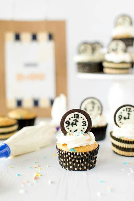 Cupcakes decorated with clocks on them that are made from cookies