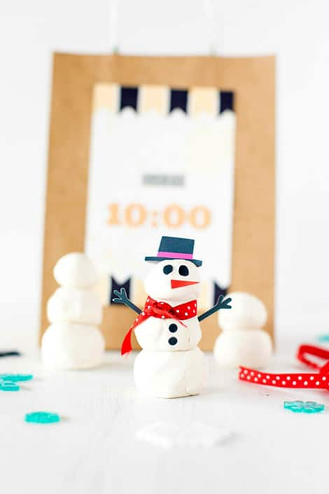 A snowman made out of white play dough in front of a 10 p.m. New Year's Eve bag