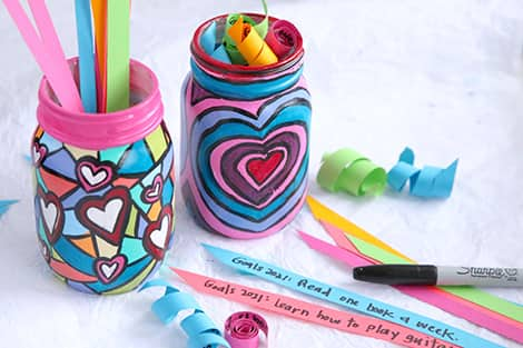 Colourful painted jars with paper spirals in them with goals