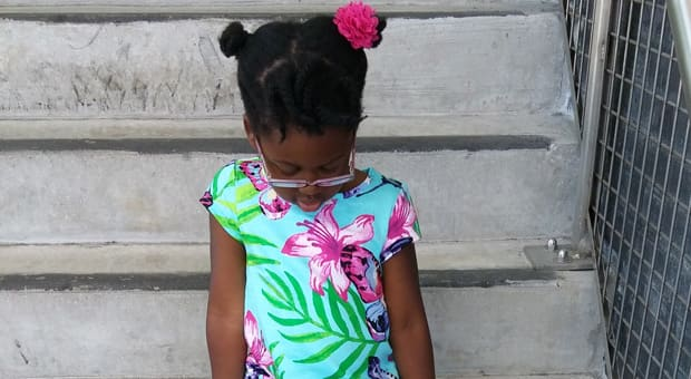 A little girl sitting on cement steps and looking down