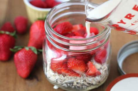 Strawberries, oats in jar with liquid.