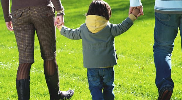 A child walking between their parents, holding their hands
