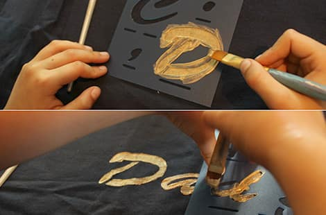 Child paints the letter D for dad.