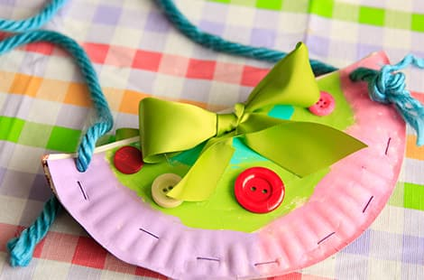 Pink purse made from paper plate with colourful buttons and bows.