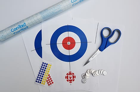 Contact paper, scissors, red/blue sticker dots and printed templates are the supplies needed to make a curling rink.