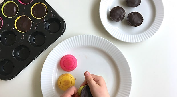 Child pops out peanut butter cups from silicon muffin liners.