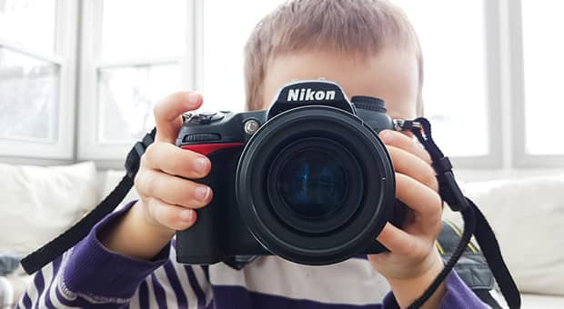 Close-up of child holding a DSLR camera.