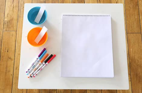 Large pad of paper, markers and two cups small bowls with two strips of paper.