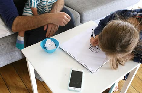 Little one draws a picture on the large drawing pad.