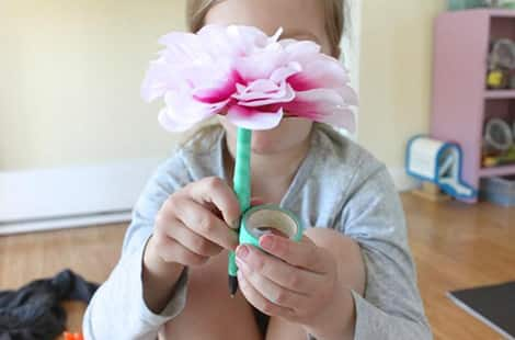 Child holds flower pen while taping.