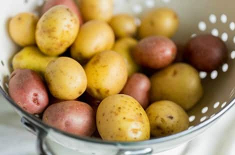 Washed potatoes in a strainer.