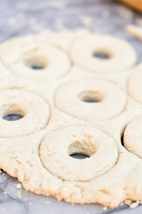 Several doughnuts in dough ready to be pressed out.
