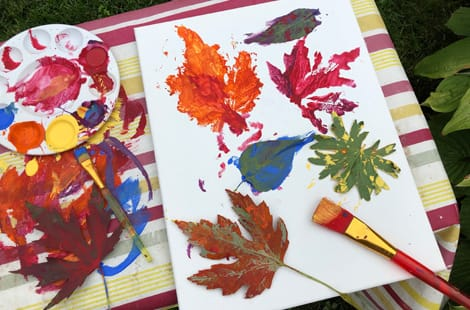 A table with paints, brushes and leaves being printed on a piece of paper