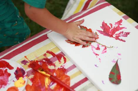 A child pressing a leaf down on the canvas with paint