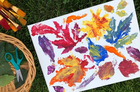A basket of leaves beside a canvas with leaf prints