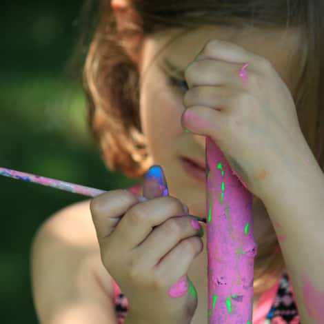 A girl painting a stick pink