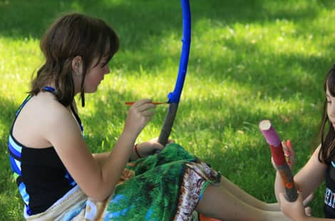 A girl painting a stick blue