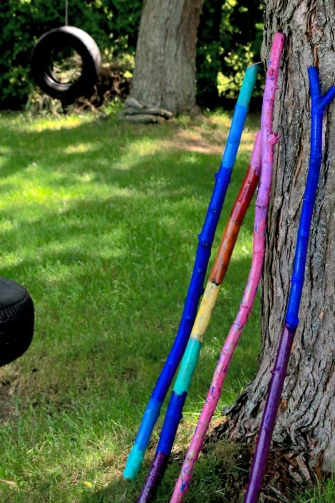 Painted walking sticks leaning against a tree