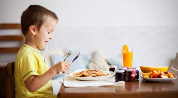 A little boy with an excited look on his face sitting down to eat some pancakes